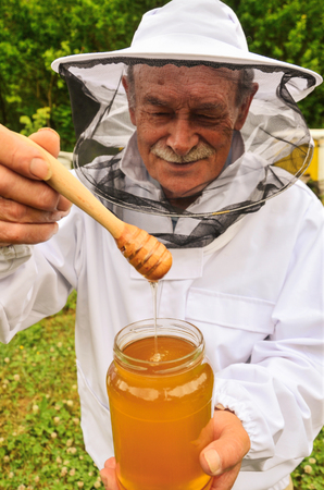 Senior apiarist presenting jar of fresh honey in apiary photo