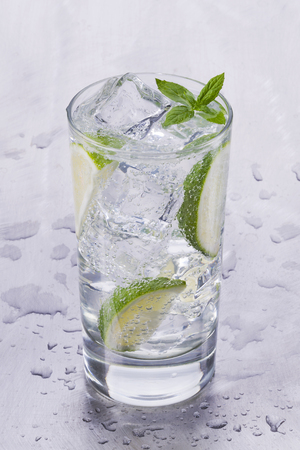 Glass of refreshing cold mineral water with pieces of lime Banco de Imagens