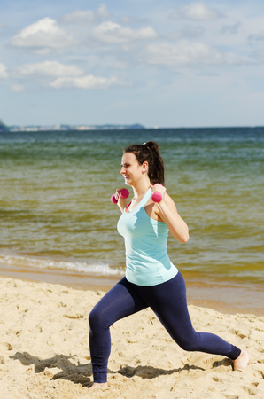 Attractive young girl exercising with dumbbells on the beach