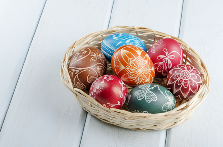 colorful scratched Easter eggs on a wooden table