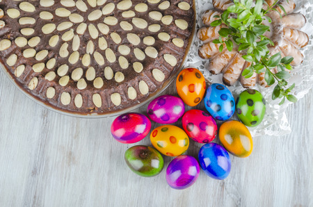 colorful easter eggs, easter cake and tulips on wooden table