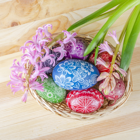 colorful easter eggs and pink hyacinth flowers on wooden table