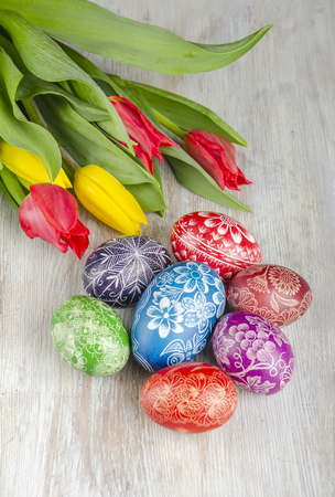 colorful easter eggs and tulip flowers on wooden table