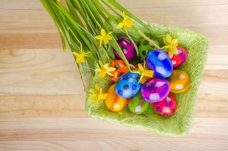 colorful easter eggs and daffodil flowers on wooden table