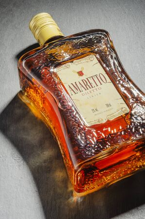 Bottle of Amaretto liqueur on stone slate background Editorial