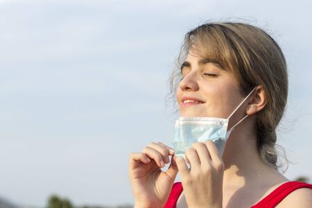 young woman wearing a face mask and red t-shirt pulling off her face mask and breathing in nature on a blue sky