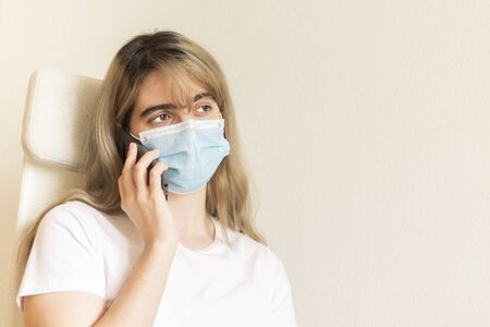 young woman with blond hair wearing a blue face mask and a white t-shirt calling through her gray mobile phone looking outside worried in a room Stock Photo