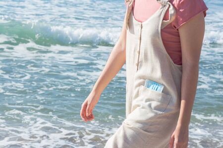 A girl with a mask in her pocket walking on the beach with the sea in the background on a sunny day