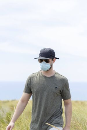 A man walking through the vegetation with a face mask, a cap and a pair of glasses on a sunny day 版權商用圖片
