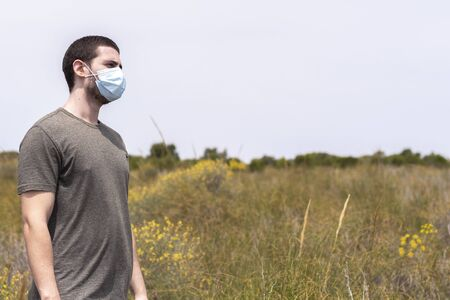 Portrait of a man standing with a face mask in nature with a blue sky on a sunny day looking to the right