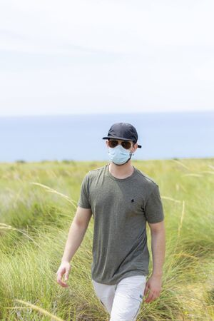 A man walking through the vegetation with a face mask, a cap and a pair of glasses on a sunny day looking at camera