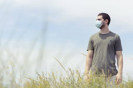 Portrait of a man standing with a face mask in nature with a blue sky on a sunny day facing left
