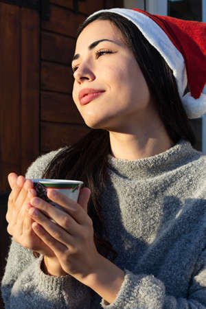 A beautiful young woman smiling holding a tea with a santa claus hat in christmas