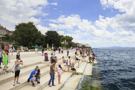 ZADAR, CROATIA - AUGUST 17, 2015: People relaxing and swimming at Zadar famoust Sea Organs. The sea organ won European Prize for Urban Public Space award in 2006.