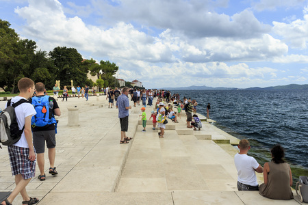 public space: ZADAR, CROATIA - AUGUST 17, 2015: People relaxing and swimming at Zadar famoust Sea Organs. The sea organ won European Prize for Urban Public Space award in 2006.