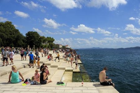 sea green: ZADAR, CROATIA - AUGUST 17, 2015: People relaxing and swimming at Zadar famoust Sea Organs. The sea organ won European Prize for Urban Public Space award in 2006.