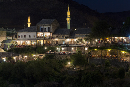 neretva: MOSTAR, BOSNIA AND HERZEGOVINA - AUGUST 13, 2015: Night photo of Tourist and locals in many restaurants over the Neretva river and mt. Hum in background Editorial