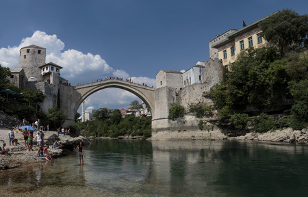 neretva: MOSTAR, BOSNIA AND HERZEGOVINA - AUGUST 05, 2015: Tourist and locals walking near Old bridge in Mostar and swimming in Neretva river. Included to the UNESCO heritag