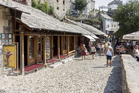MOSTAR, BOSNIA AND HERZEGOVINA - AUGUST 05, 2015: Tourist and locals walking on Old bridge and on streets of  the town of Mostar. Included to the UNESCO heritage
