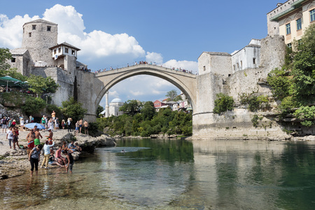 neretva: MOSTAR, BOSNIA AND HERZEGOVINA - AUGUST 05, 2015: Tourist and locals walking near Old bridge in Mostar and swimming in Neretva river. Included to the UNESCO heritage