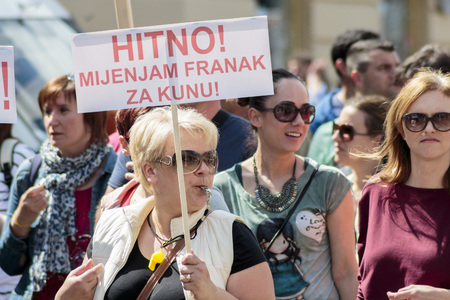 occupy movement: ZAGREB, CROATIA - APRIL 25, 2015: Woman carrying a banner during a protest against rising interest on loans in Swiss francs in Croatia, Zagreb