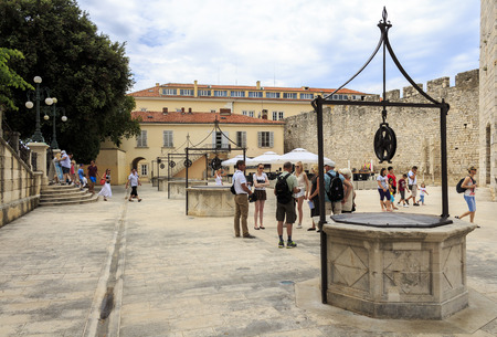informs: ZADAR, CROATIA - JULY 15, 2014:Tourist guide informs tourists about the citys sights at Five well square in Zadar, Dalmatia, Croatia