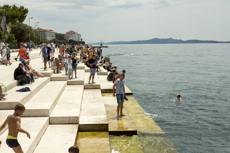 ZADAR, CROATIA - JULY 15, 2014 : People relaxing and swimming at Zadar famoust Sea Organs. The sea organ won European Prize for Urban Public Space award in 2006.