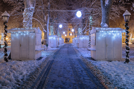 Zrinjevac park covered with snow in the cold winter night and closed stands on pathway