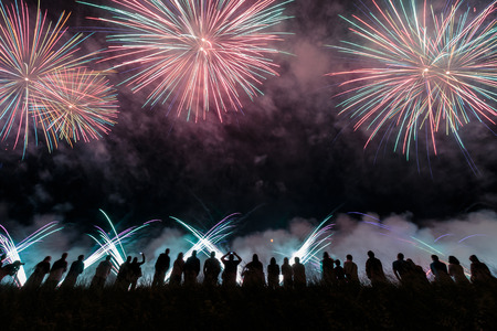 exploding: Group of people enjoying fireworks show in a carnival or holiday. People in silhouette.
