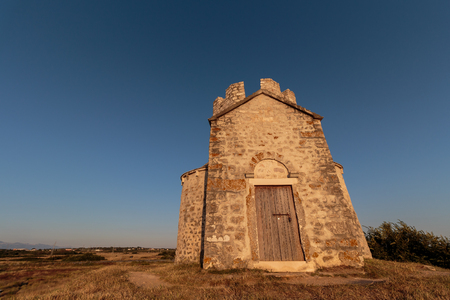 Old small stone church of St. Nicholas on hill near city of  Nin in Croatia. Golden hour Stock Photo