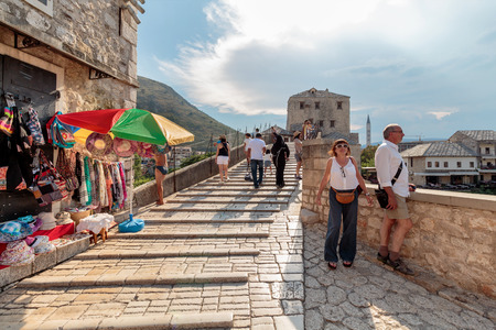 MOSTAR, BOSNIA AND HERZEGOVINA - JULY 13, 2016: Elderly couple on the Old Bridge Stari Most. Old Bridge is inscribed on World Heritage List by UNESCO in 2005.