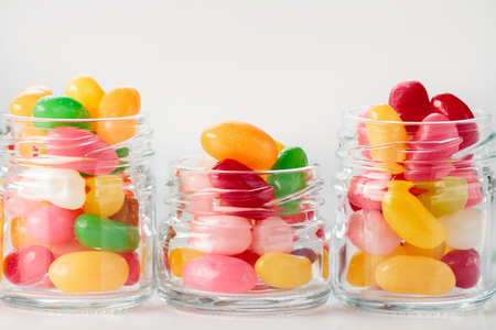 jelly beans: Jelly beans in small glass jars on white background Stock Photo