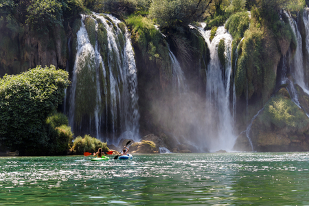 Kravice waterfall in Bosnia and Herzegovina, boy and girl in distance rowing in kayak Stock Photo