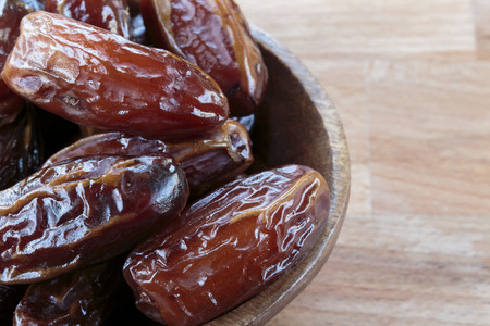 Dates fruit in wooden bowl close up, copy space Stock Photo