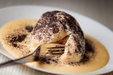Gestoomde zoete Oostenrijkse knoedels Germknodel met chocolade vulling en verstrikt met vanillesaus besprenkeld met maanzaad