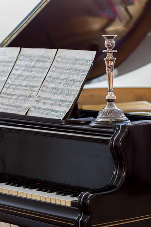 Black classic piano with silver candlestick