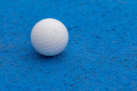 Field hockey ball on fake blue grass background