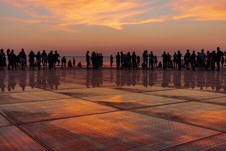 People silhouette on golden sunset in Zadar, Dalmatia, Croatia