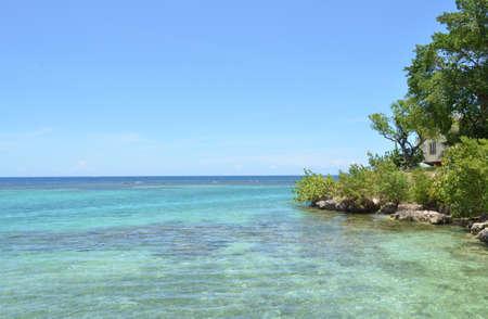 Home spähen durch die Bäume mit Blick auf die Küste in Ocho Rios, Jamaika. Standard-Bild - 85526302