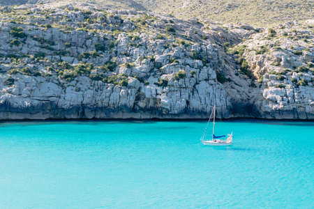 Sailing boat on blue water beach mountain background