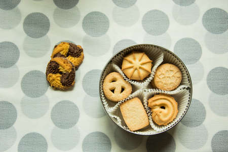 Cookies with sugar in a round box and two lying on a tablecloth with polka dots