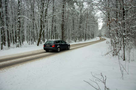 Car driving on asphalt road through the forest covered in snow - fuzzy view of the car