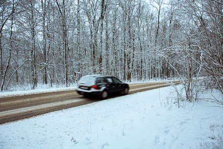 Car quickly driving through the woods to the asphalt road covered with snow - a fuzzy view of the car