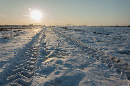 Vehicle tire tracks on snow and sun over the horizon - winter view
