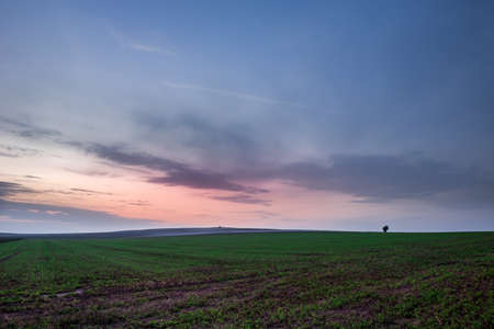 Colorful clouds after sunset over fields. Staw, Poland