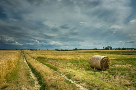 Cloudy summer landscape, rural road and hay bale in the field