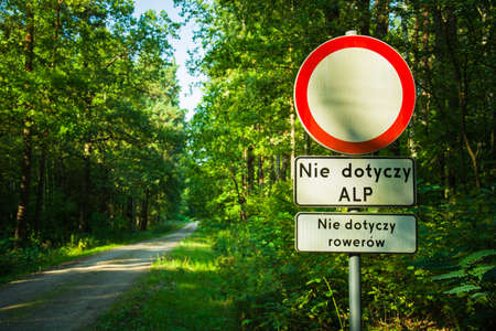 Road sign, no traffic in both directions, not applicable to the State Forests Administration, not applicable to bicycles. Text in Polish. Dirt road in the green forest
