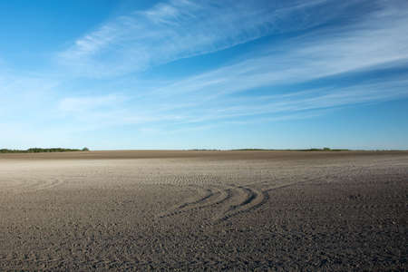 Wheel tracks on a plowed field and white clouds on a blue sky