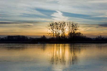 Zamarznięte jezioro, drzewa i dmuchane chmury na wieczornym niebie