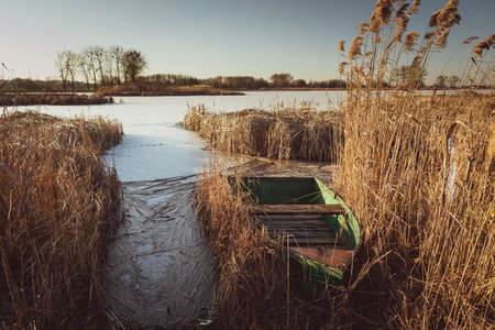 A green boat hidden in the reeds on a frozen lake